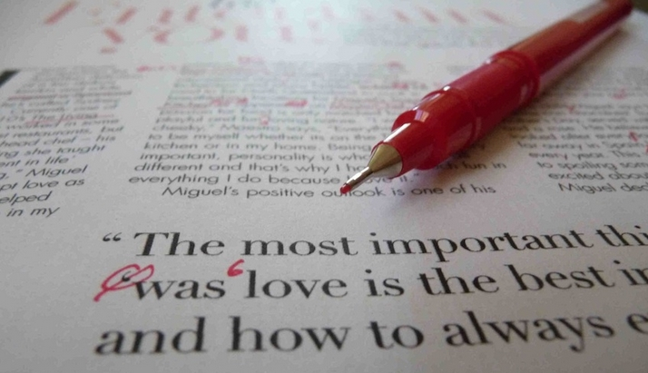 Proofreading red pen on magazine words